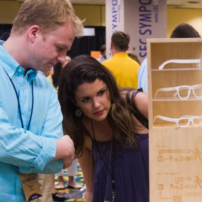 Student attendees consider an eco-friendly sunglasses concept during the student art exhibition at the 2015 SEC Symposium.