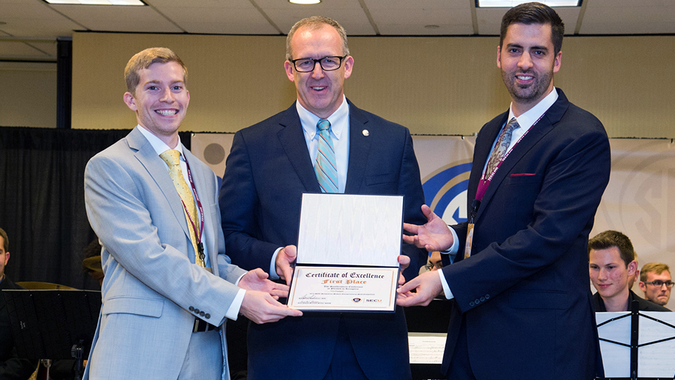 SEC Commissioner Greg Sankey (middle) presents the student entrepreneurial pitch competition's first place award to Brandon Sweeney (left) and Blake Teipel (right) from Texas A&M University during the 2015 SEC Symposium.