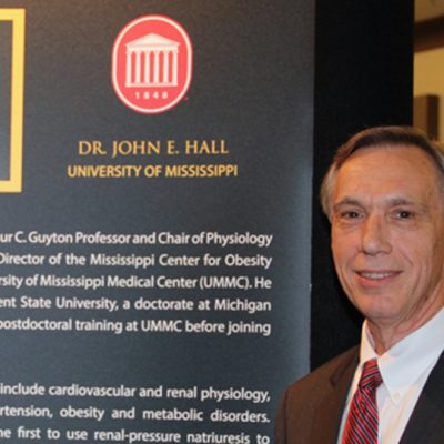 Dr. Hall stands next to his display at the 2014 SEC Awards Dinner in Destin, FL.