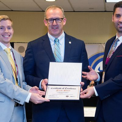 SEC Commissioner Greg Sankey (middle) presents Brandon Sweeney (left) and Blake Teipel (right) from Texas A&M University with the first place award in the student entrepreneurial pitch competition.