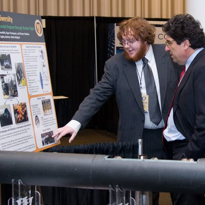 A 2013 SEC Symposium poster exhibitor presents his work to Vanderbilt University Chancellor Nicholas Zeppos.