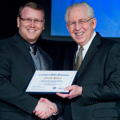 Former SEC Commissioner Mike Slive (right) presents the first place award for the Excellence in Poster Exhibition at the 2013 SEC Symposium.