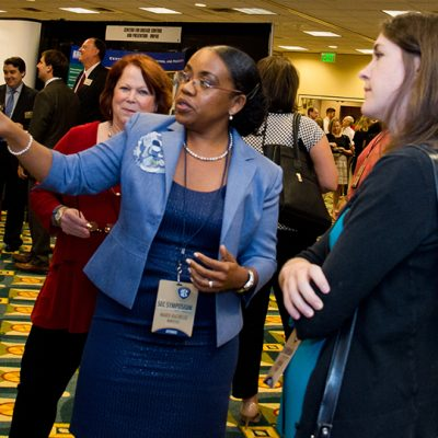 A 2014 SEC Symposium poster exhibitor presents her work to attendees.