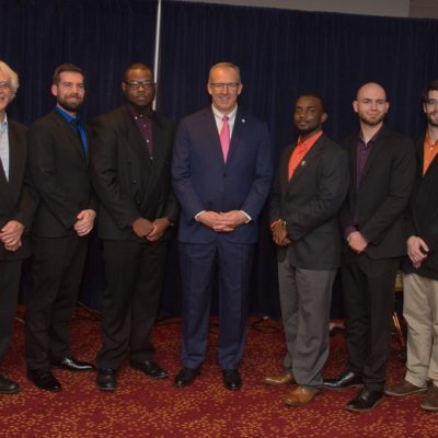 (Left to right) Kirby Davis, David D'Angelo, Erik Alvar, Lazarrus Miller, SEC Commissioner Greg Sankey, Xavier Scaife, Mason Soudelier, Ben Keith, and Michael Pendowski pose for a picture before the 2017 SEC Student Music Ensemble's performance at the annual SEC Legends Dinner.